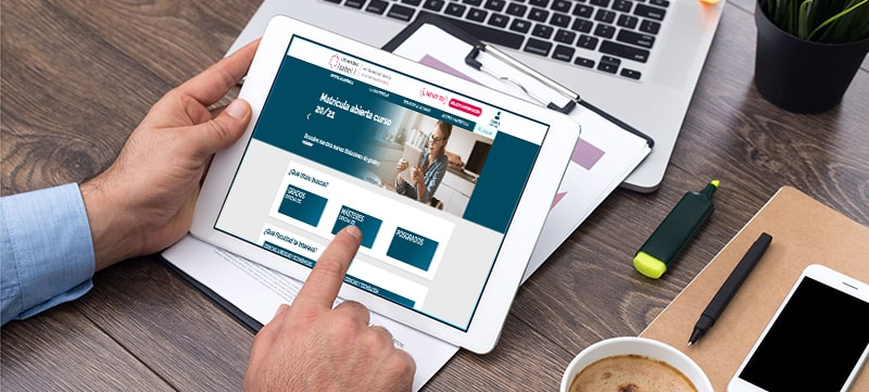 manos sobre una tableta en la que aparece la página de la Universidad Isabel I