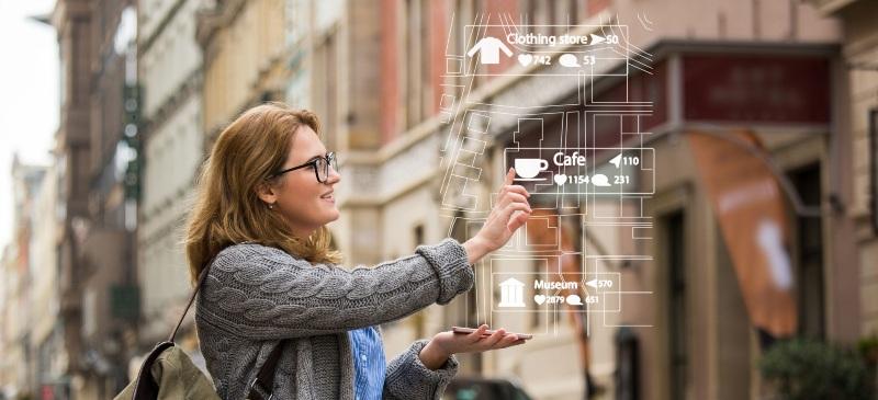 mujer con realidad virtual ante un teléfono en la calle