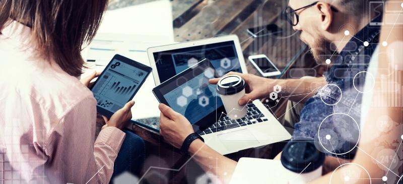 Equipo buscando soluciones ante un ordenador y una tablet en una reunión de trabajo