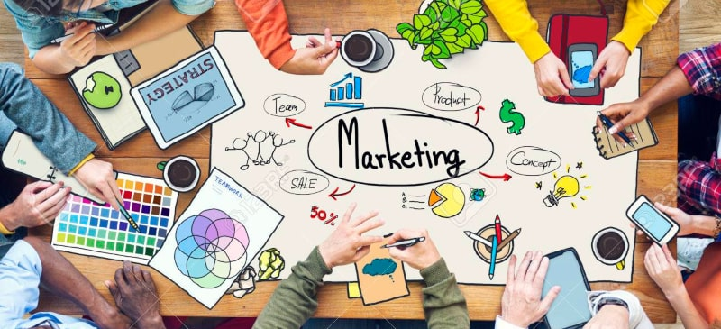 mesa con muchas personas alrededor sobre documentos de marketing