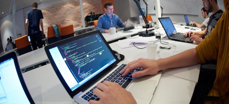 Un chico ante un ordenador en una sala de redacción. En primer plano aparece lenguaje informático