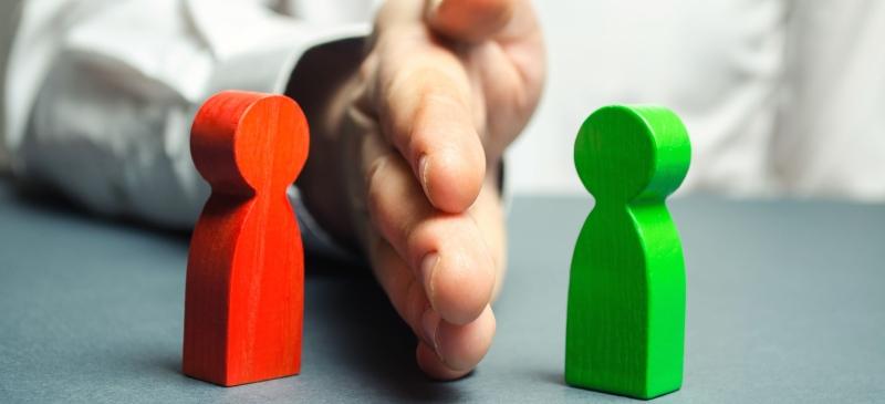Una mano separa dos muñecos de madera: uno rojo y otro verde, que ejemplifican un conflicto