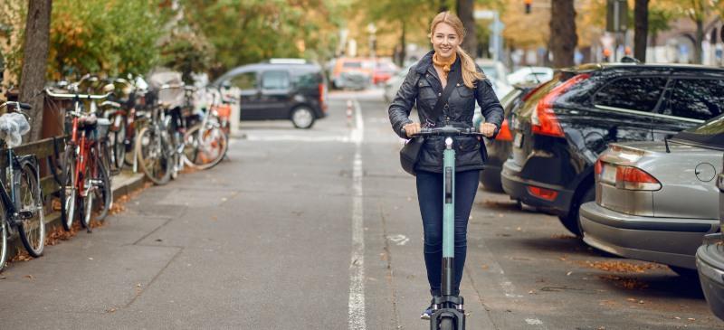 Chica en monopatín eléctrico circulando por una calzada donde hay bicicletas a un lado y coches aparcados a otro