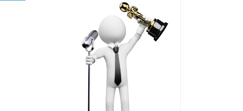 monigote levantando un oscar ante un micrófono