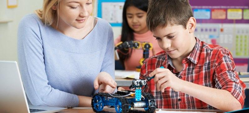 Profesora con un alumno en una clase de robótica