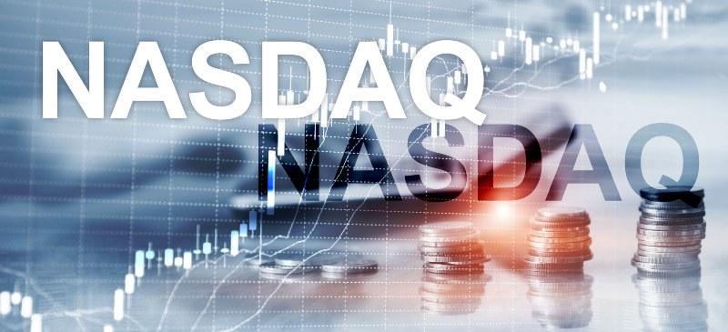 Nasdaq, con monedas y un ordenador con manos