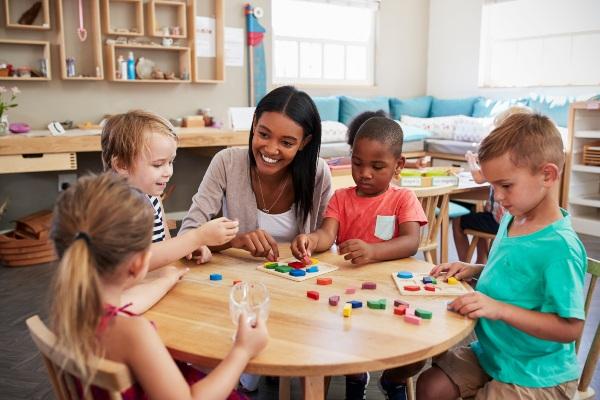 Maestra y estudiantes interactuando con materiales Montessori.