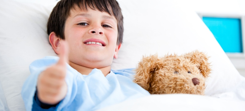 Niño con peluche subiendo el pulgar en el hospital