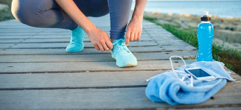 chica atándose las zapatillas en una pasarela de la playa