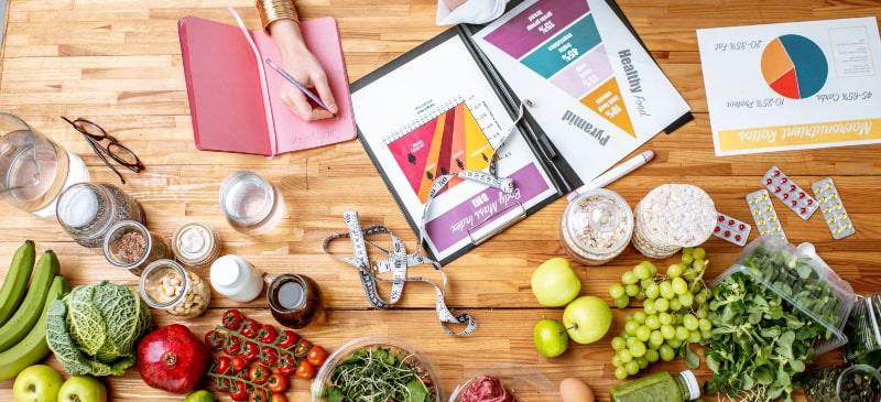 mesa llena de alimentos y una mano haciendo un estudio sobre la pirámide de alimentación