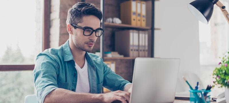 Chico con ordenador delante trabajando como periodista