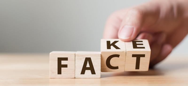 Dados de madera con las letras fact y fake, hecho y falso en inglés