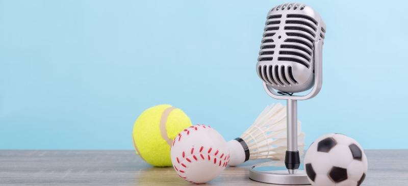 Imagen de un micrófono con varias pelotas de varios deportes