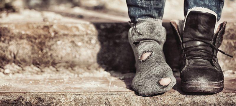 unos pies en una escalera, uno sin zapato, metáfora de la pobreza