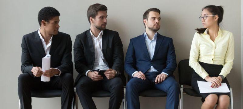 Tres hombres y una mujer esperando para una entrevista de trabajo.