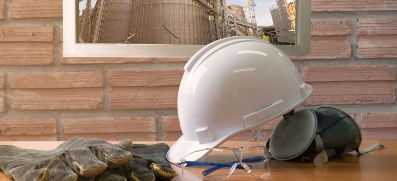 Sobre una mesa distintos materiales de protección de riesgos: casco, guantes, gafas y orejeras.