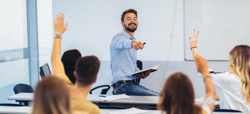 profesor de secundaria dando clase con alumnos levantando la mano para contestar