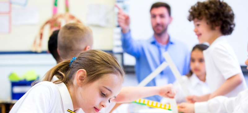 Profesor con alumnos en una clase alrededor de una mesa