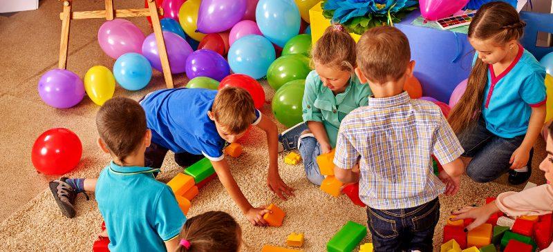 Profesora en una clase de infantil con los alumnos en la zona de juegos