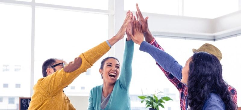 Un grupo de personas en una oficina se chocan la mano en alto sonriendo como símbolo de triunfo