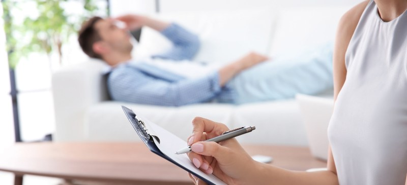 chico sobre un diván con la mano en la cabeza mientras una psicóloga toma nota