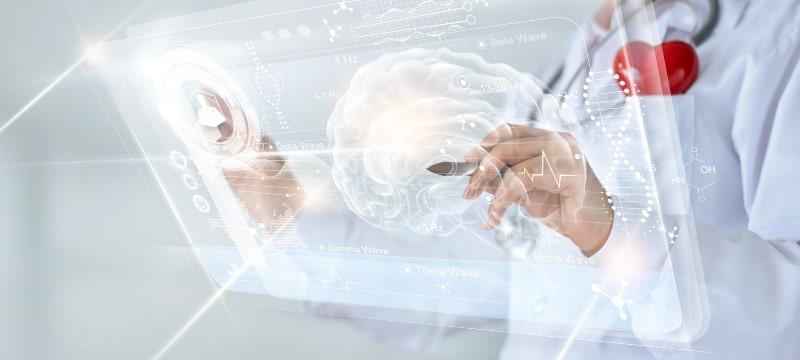 Infografía de un cerebro humano sobre el que actúan unas manos de alguien con bata blanca