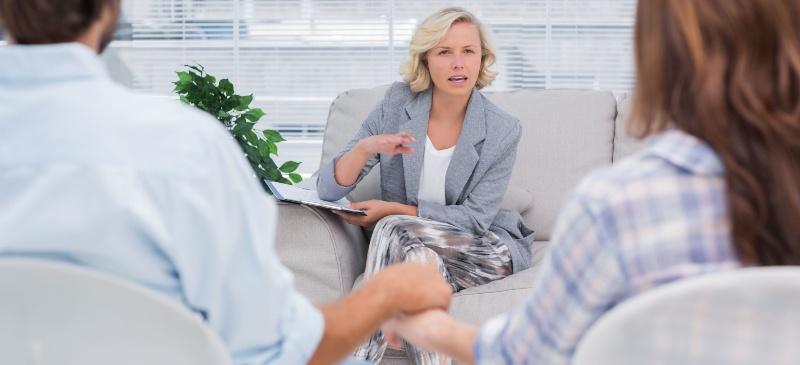 Psicología. Sesión de una psicóloga con una pareja que se da la mano.