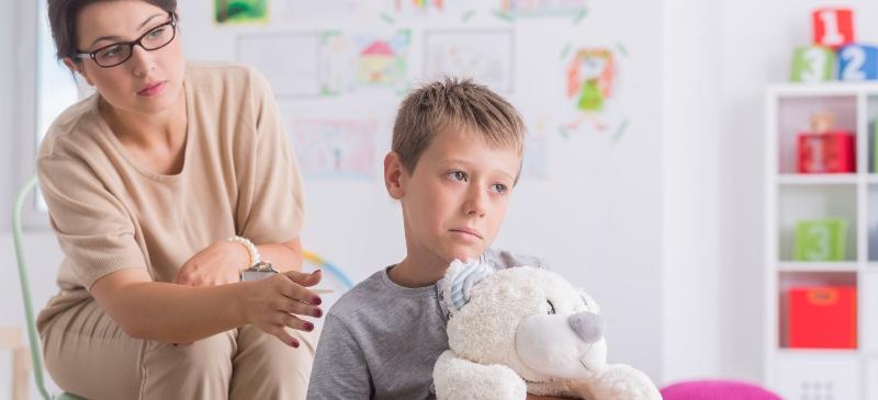 Niño con un peluche y cara de triste y una psicóloga que le pone la mano en el hombro por detrás, como muestra de apoyo