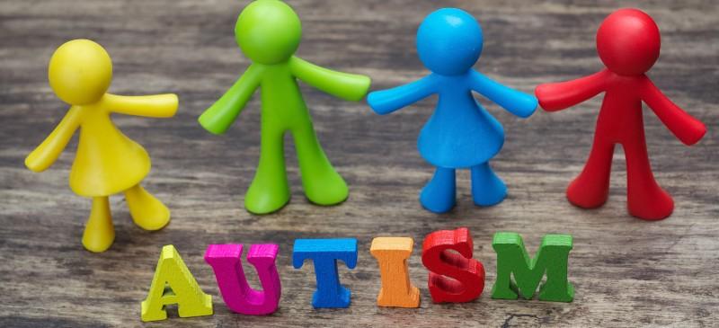 psicología y autismo. Muñecos de colores frente a la palabra autismo en inglés.
