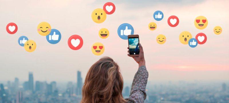 Mujer fotografiando emoticonos de redes sociales