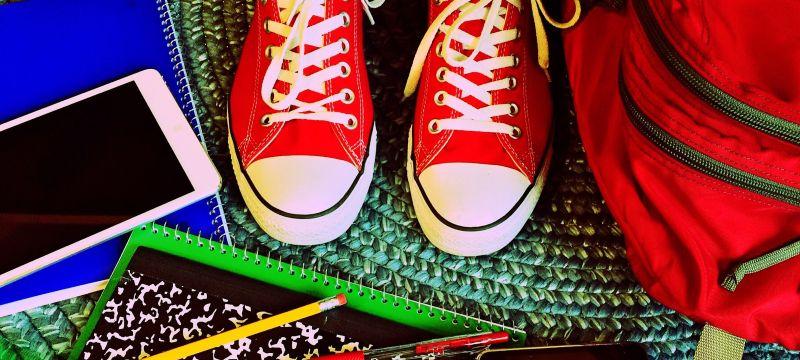 Zapatos rojos rodeados de libretas, lápices y móvil