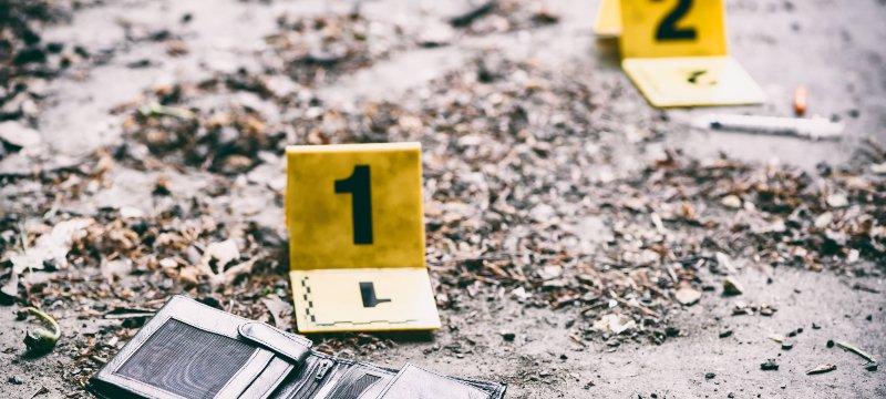 Dos marcadores de pruebas en el escenario de un crimen, uno de ellos en una cartera.