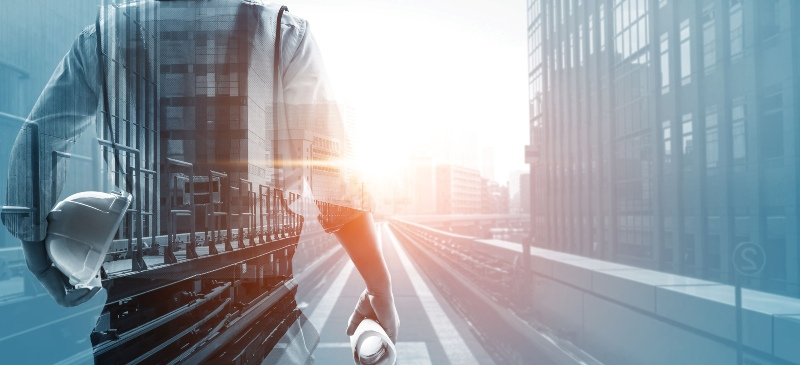 Imagen de un hombre de espaldas que se dirige hacia una industria al amanecer