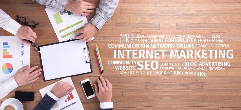 mesa sobre la que trabaja un grupo de personas. Imagen desde arriba. Letras relacionadas con marketing sobre la mesa.
