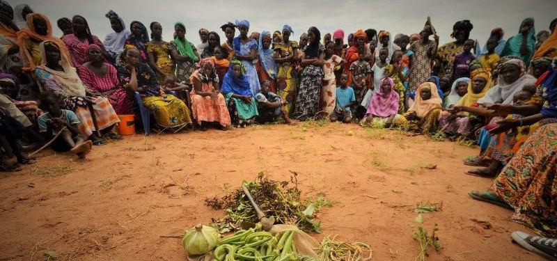 Fotografía de Fabrice Carbone. Una tribu en África frente a varios alimentos verdes en el suelo