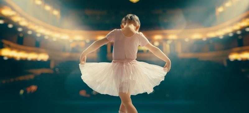 Niña bailarina saludando frente a un teatro