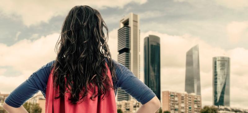 Mujer de espaldas mirando una ciudad con un traje de superman