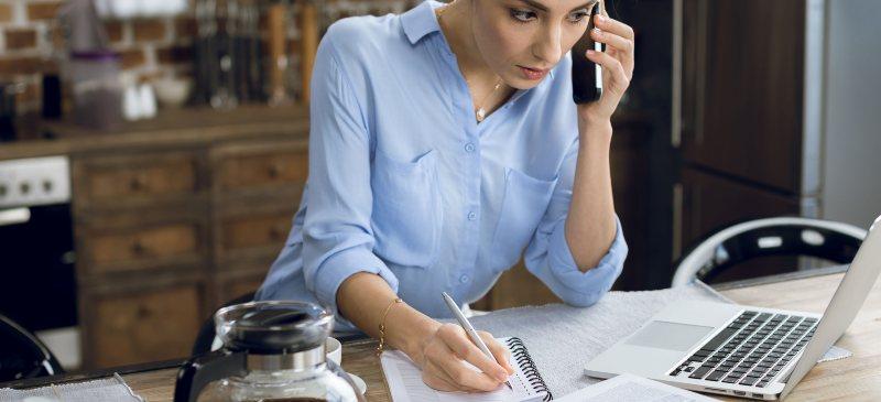 chica que en la mesa de la cocina escribe y habla por el teléfono móvil frente al ordenador