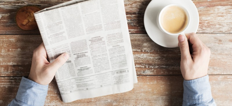 manos con un café y un periódico
