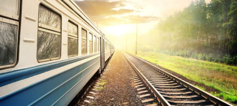 Tren pasando por un tramo de vías rodeado de campo.