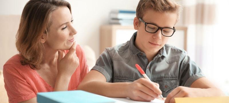 Una madre apoya en los estudios a su hijo que está con los libros sobre la mesa