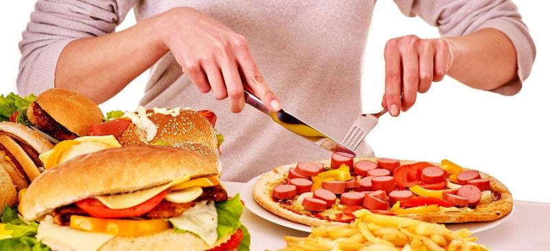 Mesa con comida asura y una mujer frente a un plato sin que se vea su rostro