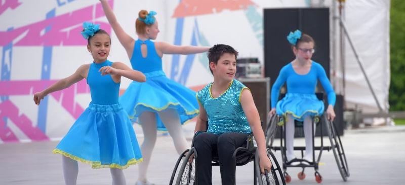 Coreografía de niños y niñas bailando, dos de ellos en silla de ruedas