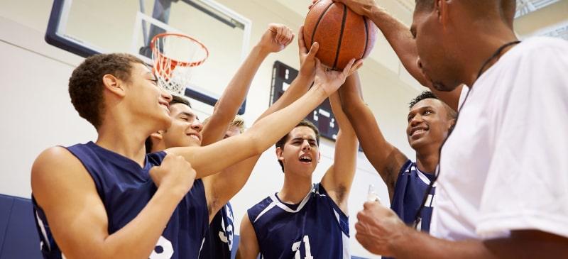 equipo de chicos con un balón en una cancha de baloncesto