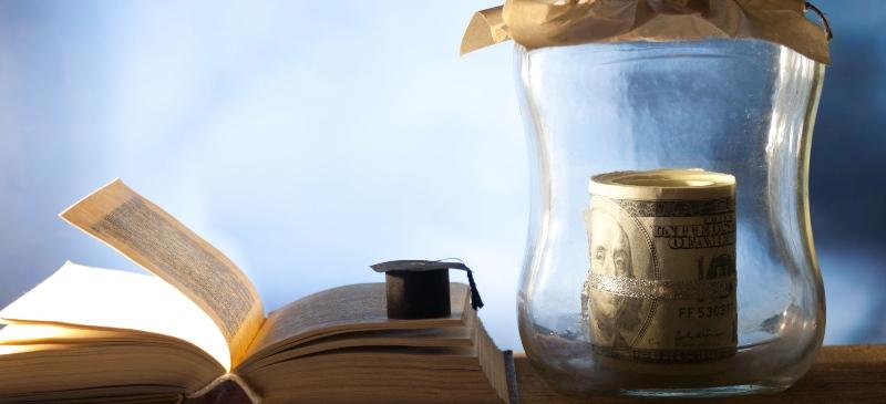Imagen de un tarro con dinero, un libro y un birrete