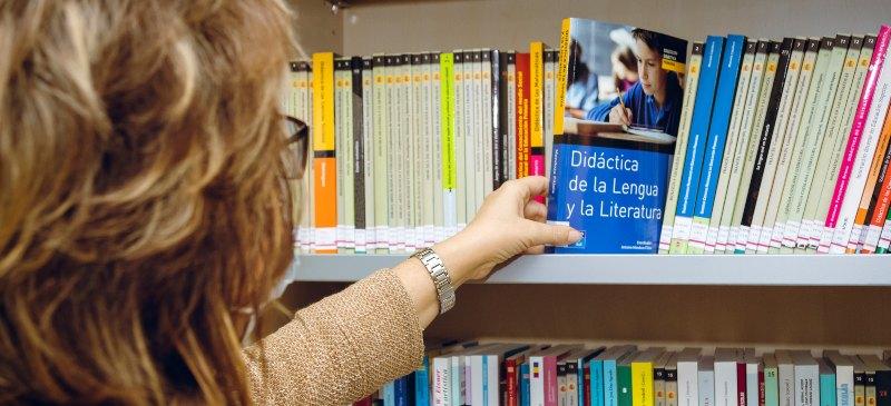 Mujer colocando un libro en la biblioteca de la Universidad Isabel I