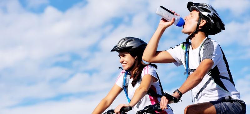 Ciclista bebiendo zumo de remolacha con su compañera ciclista al lado
