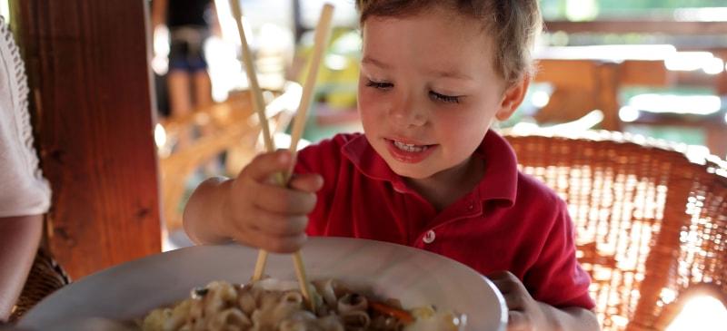 Niño intentando comer unos espaguetis con palillos
