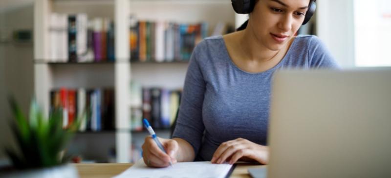 Chica estudiando un examen con cascos en su casa, preparando las oposiciones de Correos