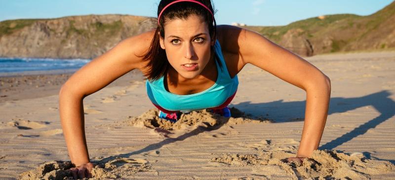 Mujer deportista haciendo flexiones en la playa
